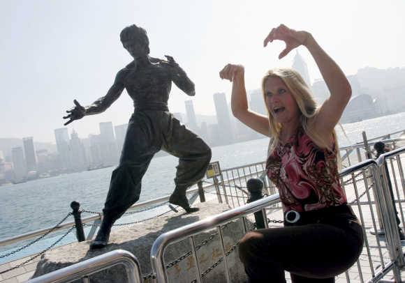 A tourist poses in front of a statue of Bruce Lee on the Avenue of Stars along the Tsim Sha Tsui waterfront in Hong Kong.