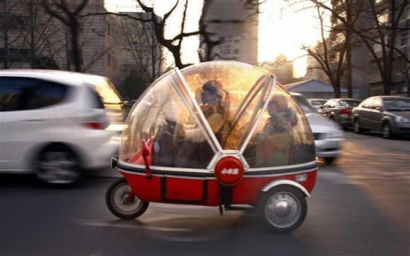 A woman and her son sit inside the capsule of an electric tricycle as they drive along a main road in central Beijing.