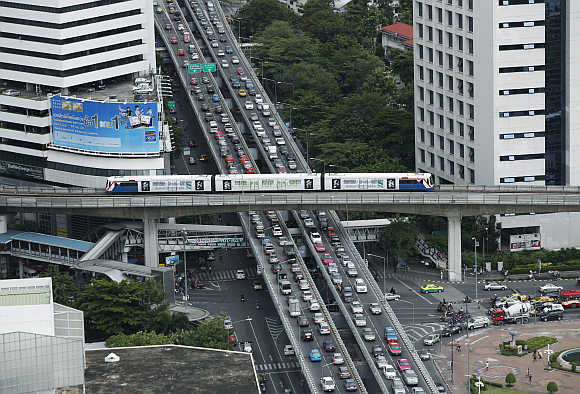 A skytrain passes over vehicles on the road during rush hour in Bangkok.