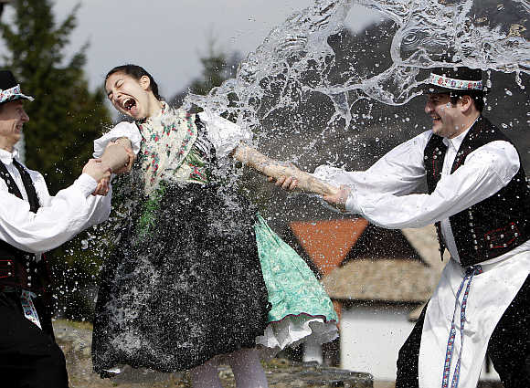 Boys hold onto a girl as they throw water at her as part of traditional Easter celebrations in Holloko near Budapest.