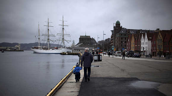 Man walks with a child near the marina in downtown Bergen.