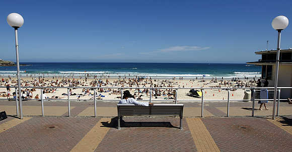 Man rests on a bench overlooking Sydney's famous Bondi Beach.