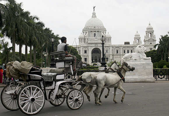 A horse-cart passes in front of the Queen Victoria Memorial in Kolkata.