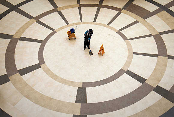 An employee cleans the floor inside a shopping mall in Mumbai.