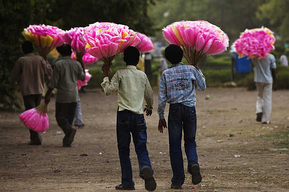 Vendors hold bags of cotton candy for sale as they look for customers in New Delhi.