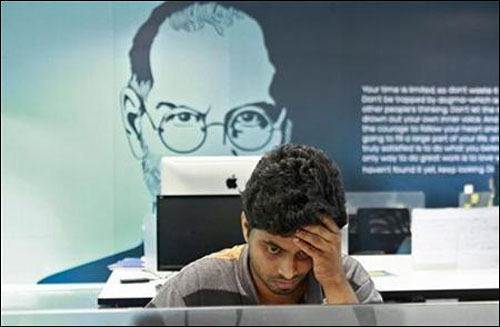 An employee works on a computer terminal against the backdrop of a picture of late Apple co-founder Steve Jobs at the Start-up Village.