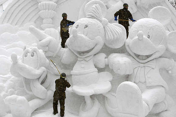 Soldiers clear snow on a sculpture at a festival in Sapporo.