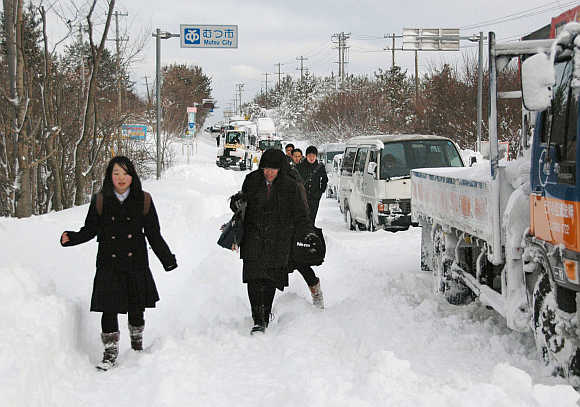 People walk past vehicles stranded in heavy snow near Niigata.
