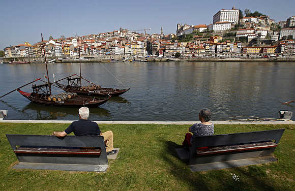 People enjoy the view along the Douro river in Porto.
