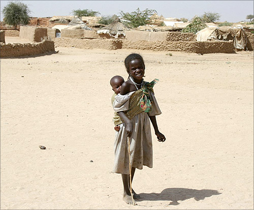 A refugee girl from Darfur carries her brother outside the International Medical Corps' clinic at Mile refugee camp in eastern Chad.