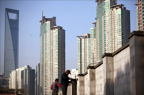 Workers build walls at a construction site at Pudong Lujiazui financial area in Shanghai.