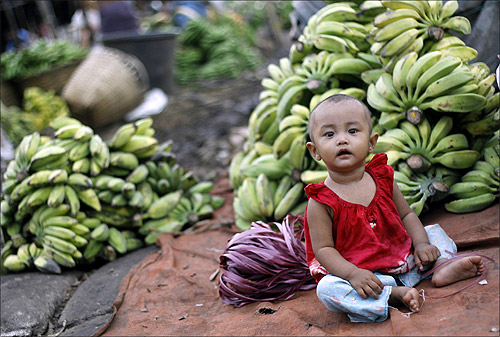 A toddler sits infront of piles of bananas at a shop in a market in Yangon.