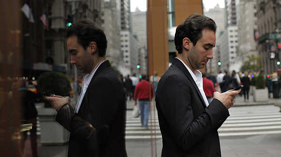 A man types on his mobile phone in New York.