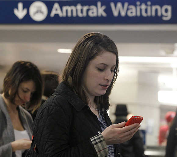 People look at their mobile phones as they wait to board trains at Penn Station in New York.