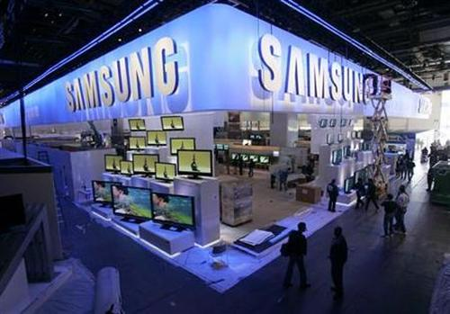 A worker cleans the sign hanging over the Samsung booth