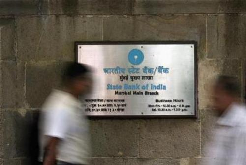 People walk in front of a signboard displayed at the head office of State Bank of India in Mumbai