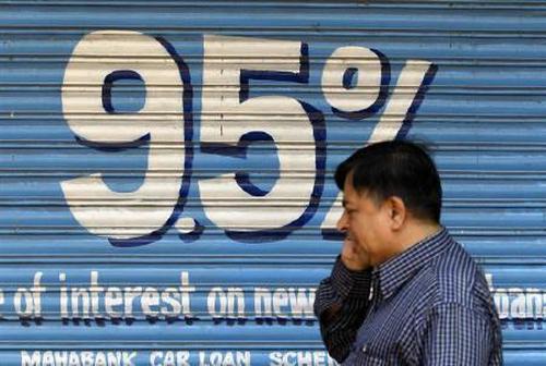 A man walks past a bank advertisement for loans