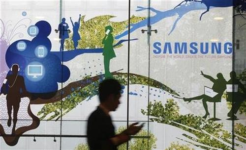 A man using a mobile phone walks past a Samsung Electronics' advertisement in Seoul