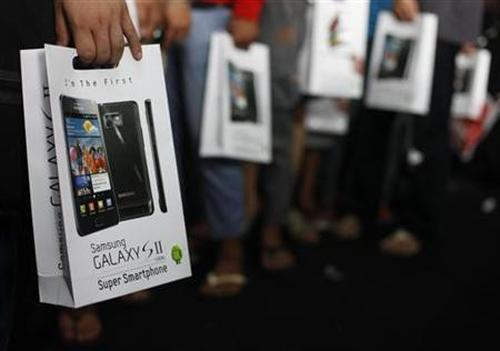 Customers hold their newly purchased Samsung Galaxy phone in Jakarta