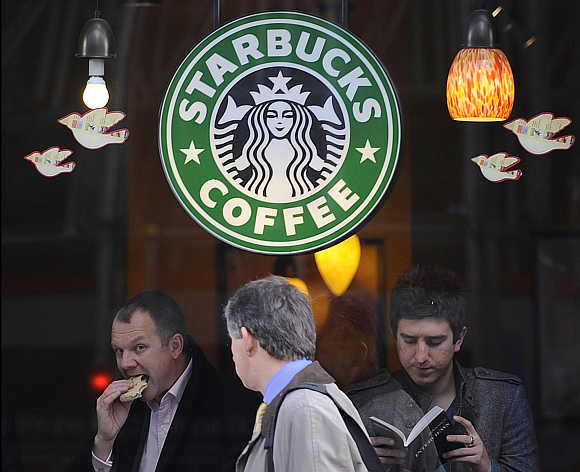 A pedestrian passes a branch of Starbucks Coffee in central London.