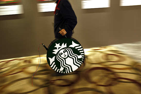 A man carries a Starbucks logo sign after a corporate event at a hotel in Shanghai.