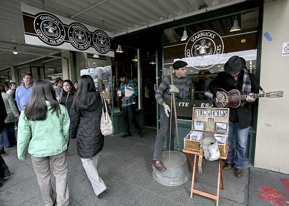 Tourists walk by as street musicians Slimpickins play in front of the first Starbucks store located at historic Pike Place Market in Seattle, Washington.