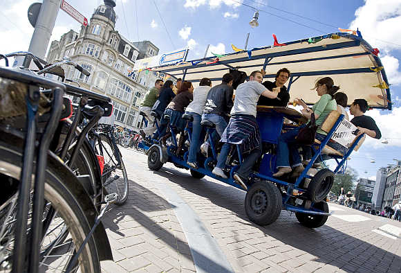 Tourists cycle as they drink beer and sing karaoke on a beerbike in Amsterdam.