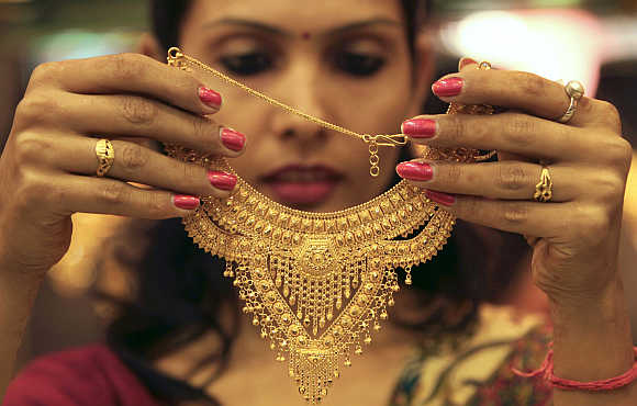 A salesgirl shows a gold necklace to customers at a jewellery s