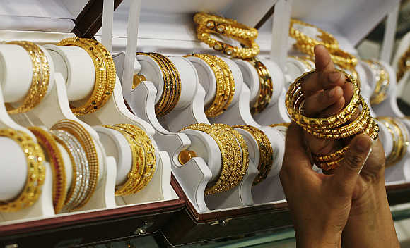 A customer tries gold bangles inside a jewellery showroom in Noida.