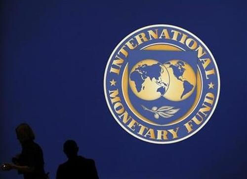 Visitors are silhouetted against the logo of the International Monetary Fund.