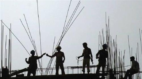 Indian labourers work on a high-rise building construction site in Kolkata