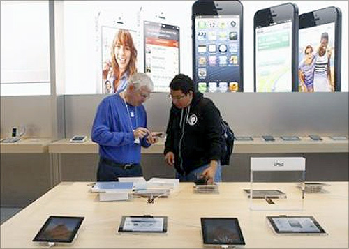 A customer is helped by an Apple employee while looking over the iPad mini after the device went on sale at Apple's retail store in Palo Alto.