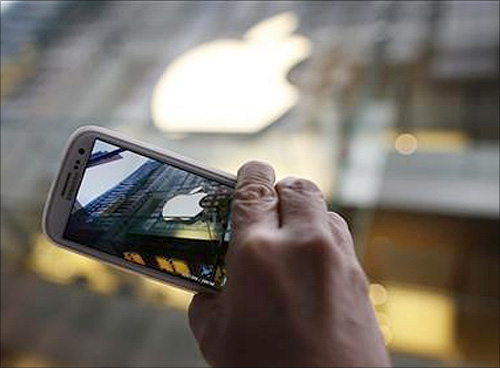A passerby photographs an Apple store logo with his Samsung Galaxy phone on the morning iPhone 5 goes on sale to the public in central Sydney in this September 21, 2012 file photograph.