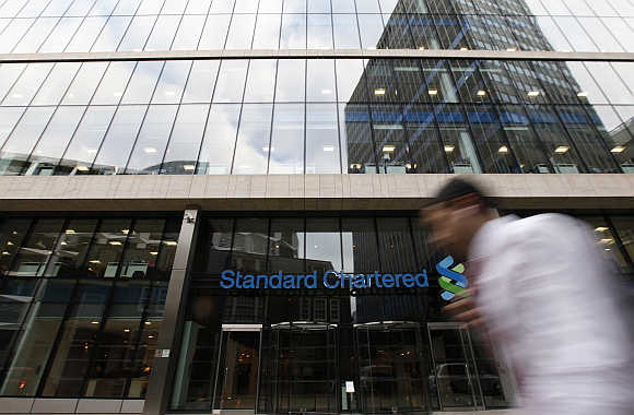 A man walks past a Standard Chartered bank in London.
