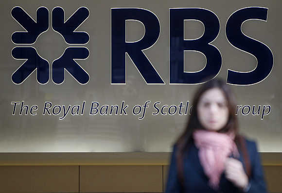 A woman leaves a Royal Bank of Scotland building in London.
