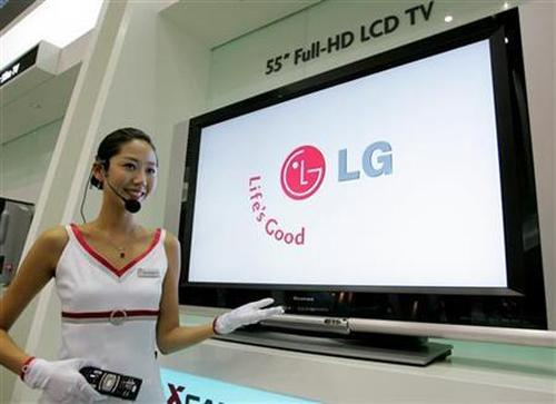 A saleswoman demonstrates the use of an LG Electronics 55-inch Full-HD LCD TV