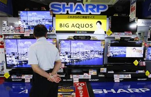 A man looks at Sharp Corp's Aquos TVs displayed at an electronics store
