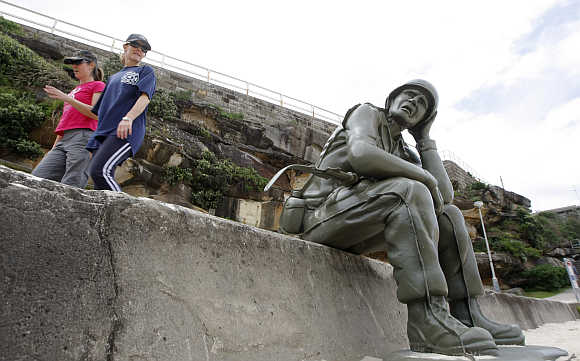Two women walk past a work by artists Bellotti and Rosewell, which is part of 'Sculpture by the Sea', near Bondi Beach.