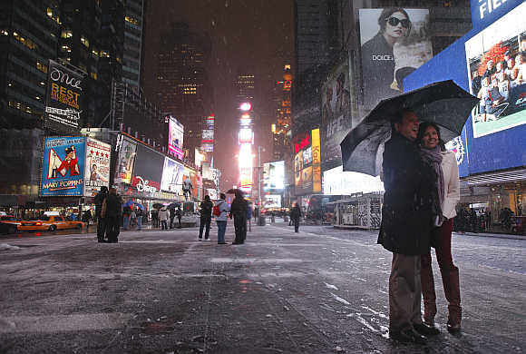 A couple have a picture taken during a snow storm in New York's Times Square.