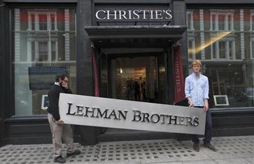 Christie's employees pose for a photograph with a Lehman Brothers sign