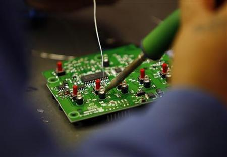 A worker solders a circuit board