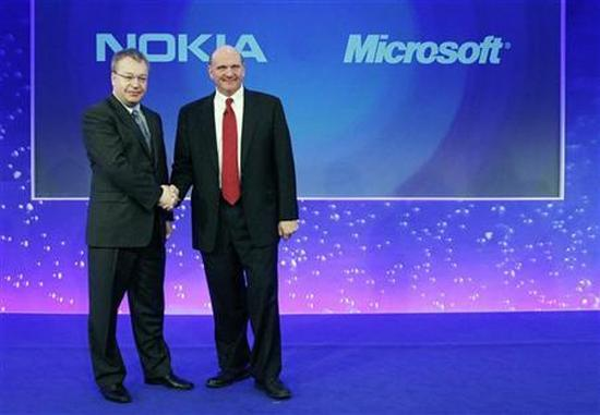 Nokia chief executive Stephen Elop (L) welcomes Microsoft chief executive Steve Ballmer with a handshake at a Nokia event in London