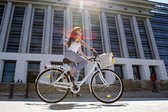 A woman rides her bicycle past Romania's National Library in Bucharest.