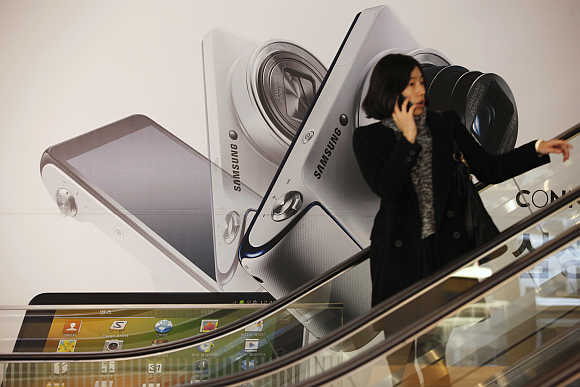 A woman talks on her phone in front of an advertisement promoting Samsung Electronics' Galaxy Camera in Seoul.