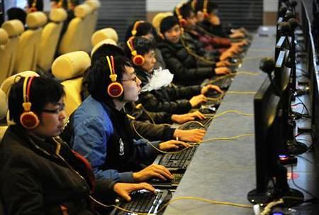 A file photograph shows a man smokes while using a computer at an Internet cafe in Taiyuan, Shanxi province.