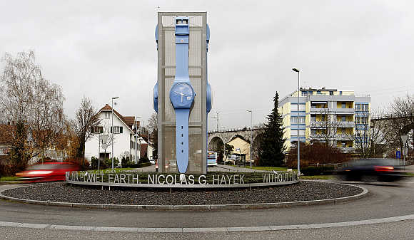 Cars drive past a giant Swatch watch placed in the centre of a roundabout in Swiss town of Grenchen.