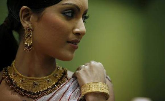 A model poses with gold jewellery during a jewellery show.
