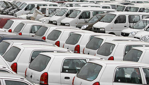 A worker adjusts the windscreen wipers of a parked car at a Maruti Suzuki stockyard on the outskirts of Ahmedabad.