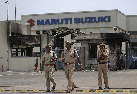 Police officials walk outside the Maruti Suzuki's plant in Manesar.
