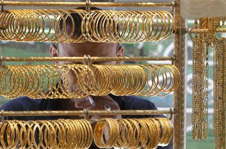 A man looks at gold jewellery in Amman, Jordan.